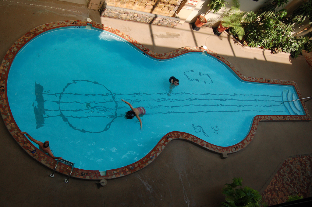 swimming pool in shape of acoustic guitar with blue clear