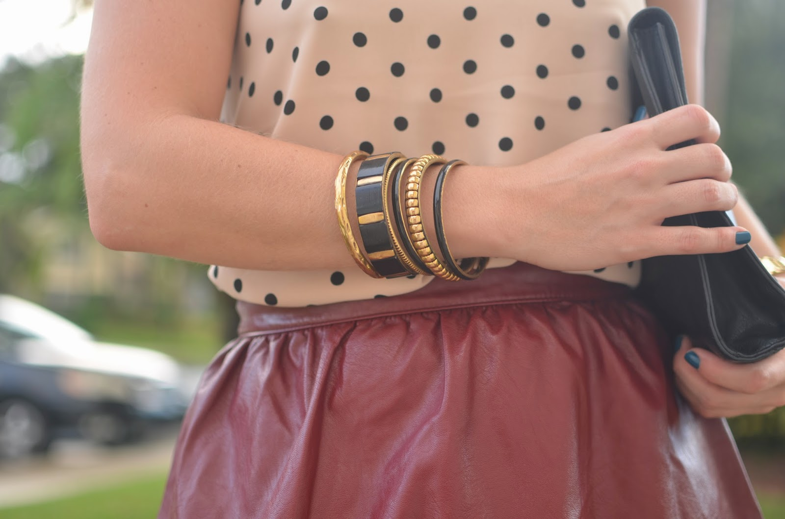 Burgundy leather skirt - polka dot top - black clutch - bangles