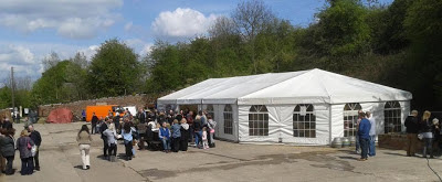 A large marquee in a concreted yard, with trees in background, has people spilling out of it into the sunshine enjoying drinking real ale.  There are some casks at one end of the tent, empties maybe?