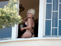 Courtney Stodden sitting on a window in a thong bikini