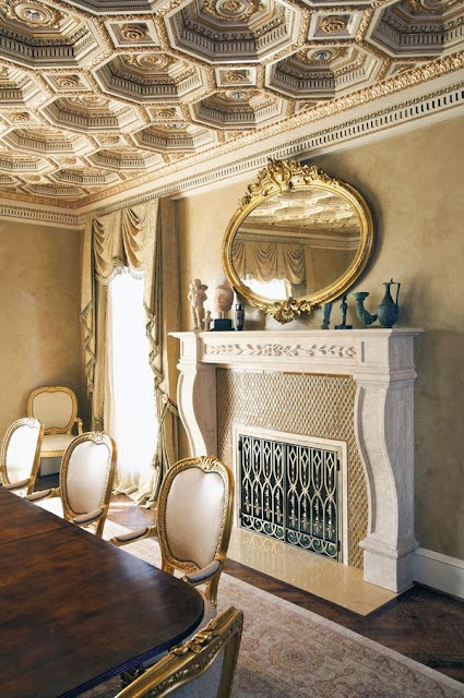 regal and elegant dining room with sophisticated details on the ceiling, dining chairs, and fireplace accopany it