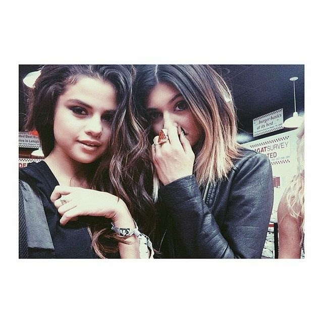 "Selena Gomez and Kylie Jenner typing their images:‭ ""‬In n out for lunch five guys for dinner‭ ‬#girlstrip.‭"""