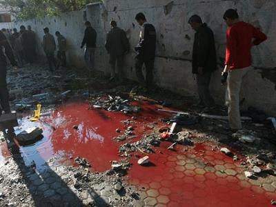 Palestinos passam por poças de sangue após ataque israelense