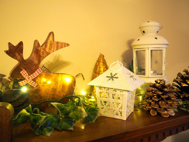 Christmas decorations in the living room, with wooden reindeer, snowflake lanterns, pine cones, leaves and lights