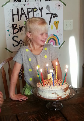 a smiling little girl getting ready to blow out birthday candles on her cake