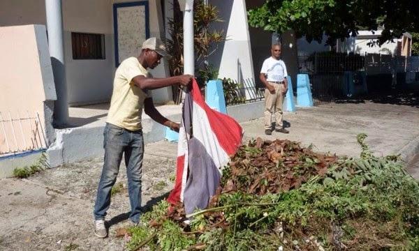 En San Juan: Un empleado del gobierno usa la Bandera Nacional como trapo para recoger basura
