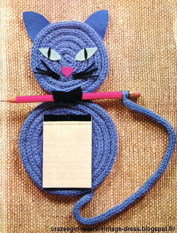 LE CHAT PENSE-BETE  Voici un chat sérieux et de bonne compagnie, qui vous aidera à ne plus rien oublier!  MATERIEL  •  Un peu de carton fort.  •  Un compas pour tracer la forme.  •  De la laine de grosseur moyenne (couleur au choix).  •  Un peu de feutrine rosé, verte, noire et de la couleur du chat.  •  Un   crayon de teinte contrastant avec la laine.  •  Un petit carnet bloc-notes.  •  Une petite attache pour sous-verre.  •  De la colle cellulosique  REALISATION  •  Dessiner le chat sur le carton  comme le montre le croquis. Découper.  •  Faire une chaînette de longueur suffisante pour enrouler et recouvrir la tête et le corps du chat. La longueur dépend de la grosseur de la laine employée; à titre  indicatif,  nous avons utilisé 1 m, 20 pour la tête et le double pour le corps.  •  Faire une chaînette de 30 cm pour la queue.  •  Enduire le carton d'une mince couche de colle.  Laisser sécher puis recommencer.  •  Enrouler alors la chaînette en commençant à la poser par le centre du cercle. Continuer l'enroulement en collant au fur et à mesure. Cacher l'extrémité sous le dernier rang.  •  Enrouler ainsi le corps et la tête.  •  Cacher  et  coller  l'extrémité  de   la  queue sous les derniers rangs du corps.  •  Coller le fil de l'extrémité de la queue autour du crayon.  •  Découper la feutrine comme  le  montre  le croquis pour faire les oreilles, les yeux, le nez. Coller en place.  •  Découper dans la feutrine noire une petite bande de 1,5 cm  x 3,5 cm. La rouler autour du crayon et la coller pour la maintenir fermée en anneau. La coller sur le « cou »  du chat.  •  Coller un petit carnet sur le corps.  •  Fixer derrière le chat l'attache pour sous-verre afin de pouvoir le suspendre. vintage cat reminder 1970 70s 1972