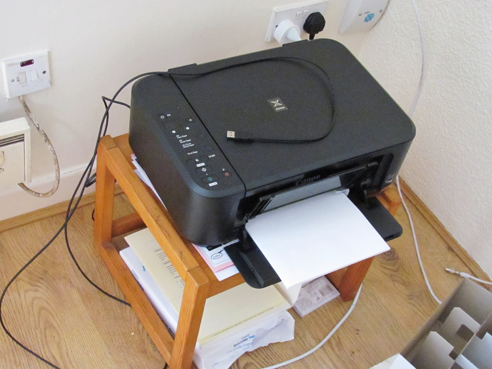 The printer, manuals, and printer paper on a footstool and the floor