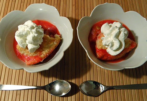 Two bowls of cobbler with cream and two spoons