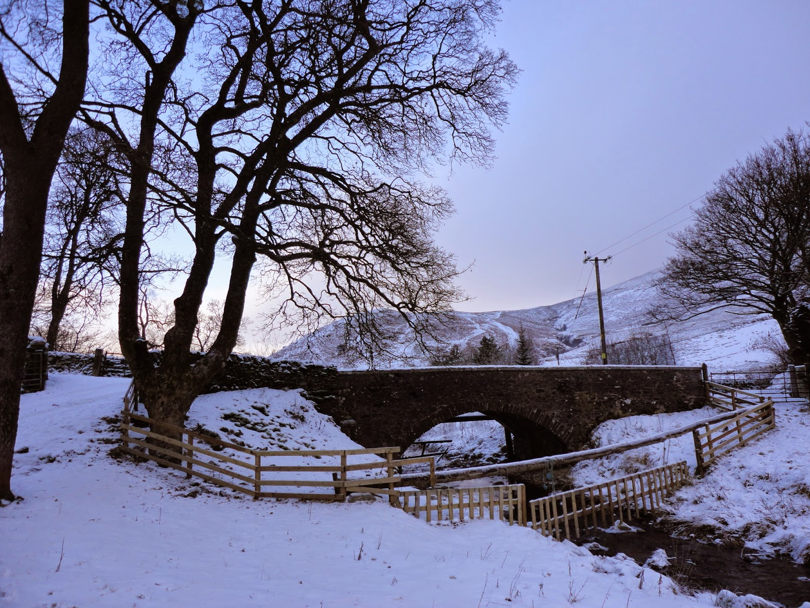 country farm landscape with trees, hills, river, bridge and snow in winter in scotland