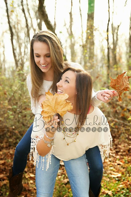 best friend girls piggy back laughing and playing with fall leaves