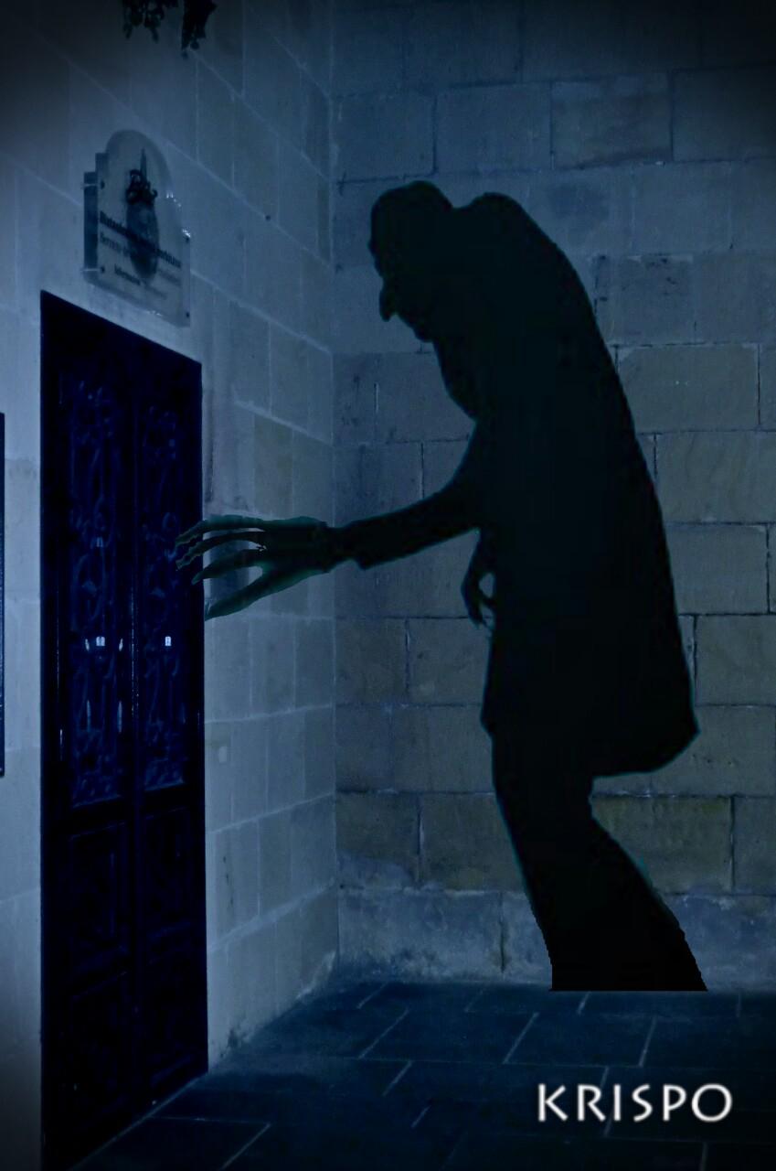 sombra de nosferatu al lado de puerta por la noche