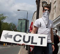 cult sign held by protester in london