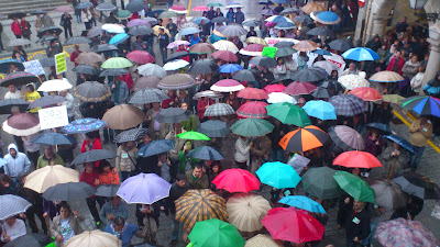 Imagen de lso manifestantes con paraguas en la plaza Mayor