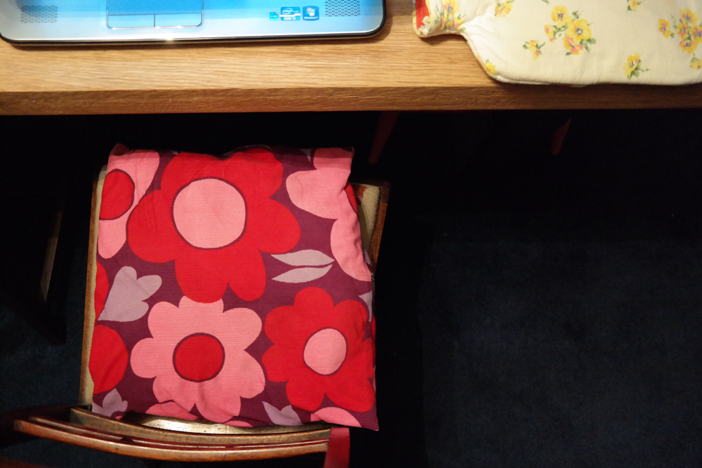 Laptop, hot water bottle and cushion on a dining room chair