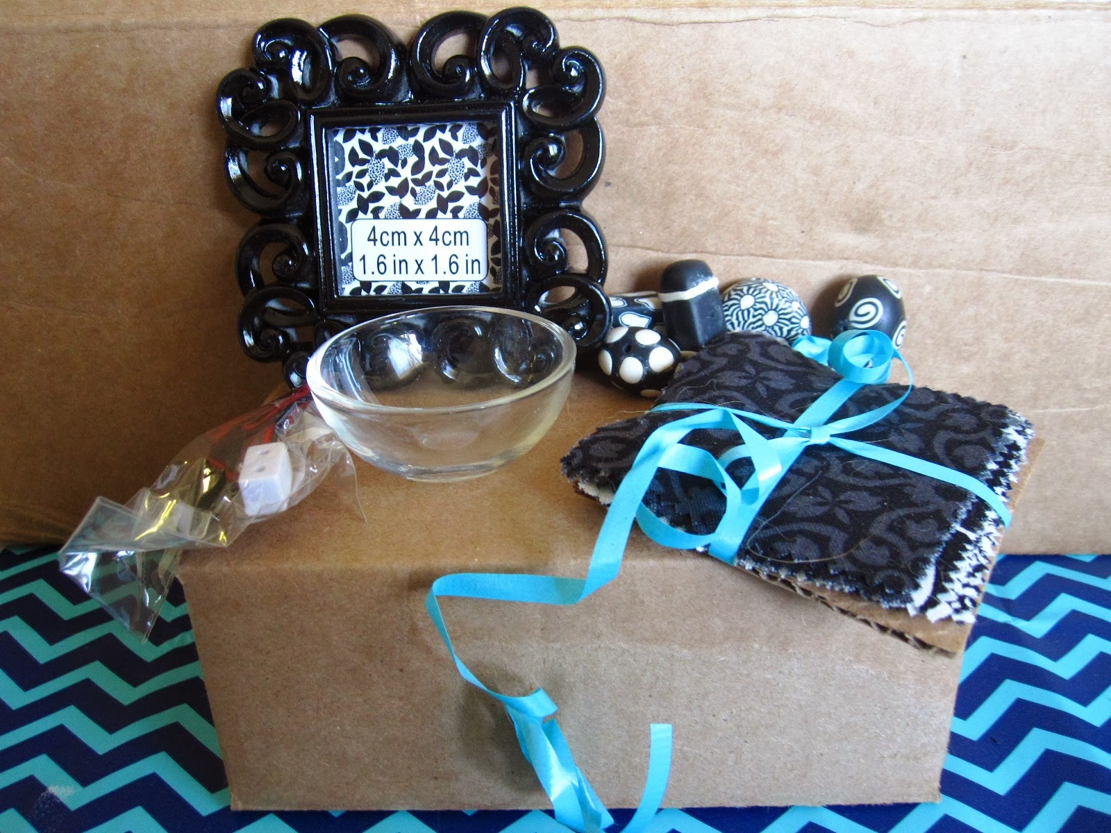 Black and white modern miniature picture frame, bowl, beads, fabric pieces and battery adapter