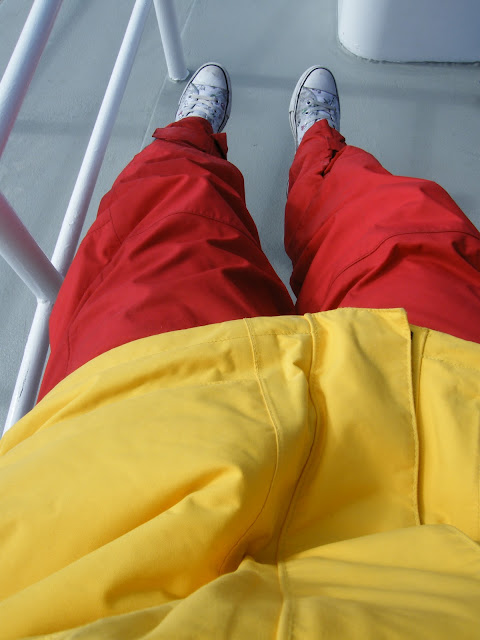 Female wearing red and yellow oversized sailing gear with Converse sneakers.
