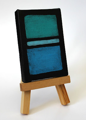 blue and green color field painting on an easel
