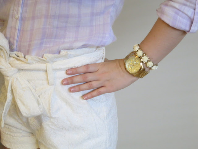 Close up of cream lace shorts, purple plaid shirt, gold watch and cream bracelet.