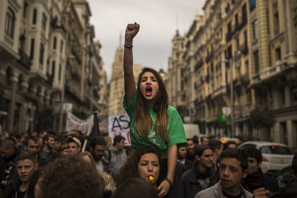 70 Of The Most Touching Photos Taken In 2015 - Students shout slogans as they march during a student strike in Madrid, Spain.