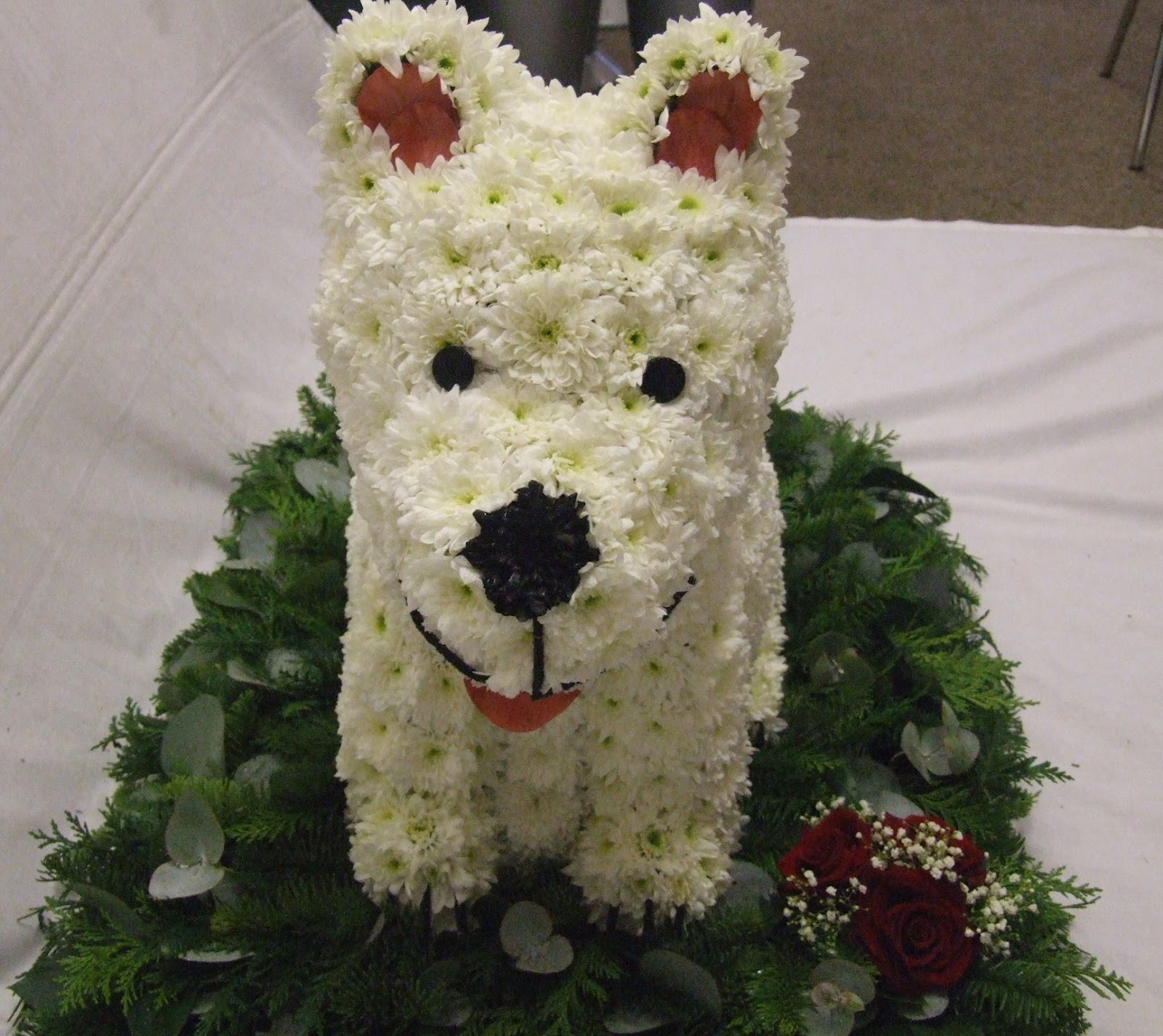 Rjs florist 3d westie tribute are made out of various fabrics and the button nose is a flower sprayed black the collar is a proper dog collar main colour red with silver bones on izmirmasajfo