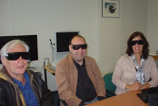 Fotografia de 3 Técnicos da Fundação Sain a experimentarem óculos com várias percentagens de bloqueio da luz