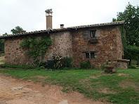 La façana de llevant amb la peculiar finestra doble amb reixa de llangardaix del Mas Romeu