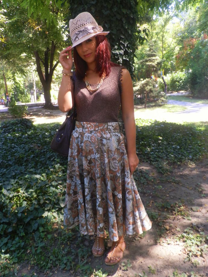 Outfit I am wearing: Full printed skirt in earth fall tones made by me; Chocolate brown sleevless top hand-knitted by my mom; Handmade big dark brown leather purse; pink straw hat, nude sandals with crystals & brown and golden jewelry from H&M