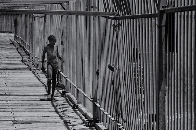 A boy walks on the pier in Strand Western Cape - Street photograph