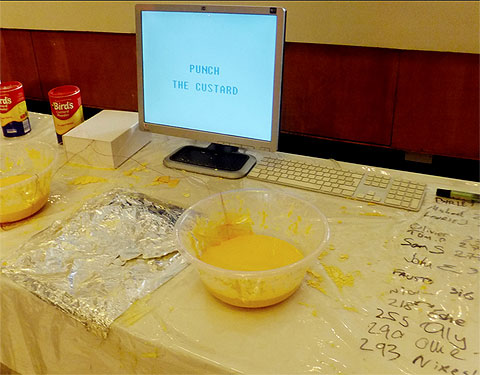 "Image of a computer screen, that reads ""Punch the custard"" on a table with two bowls of custard, scribbled scores, and a touch-pad of tin-foil that completes a circuit when punching the custard."