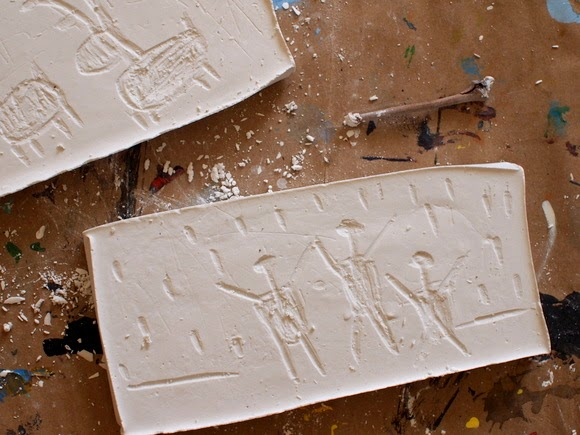 Carve plaster of paris like a rock with a twig