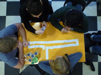 Vogelperspektive: Gelber Tisch und junge Leute, die Domino spielen, die Erste