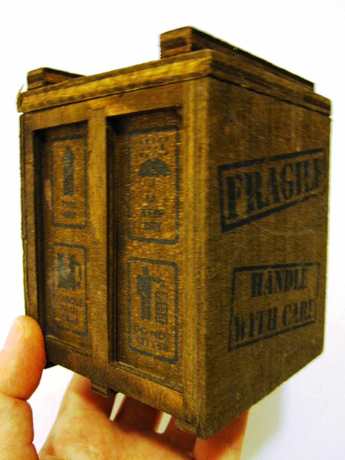 A hand holding up a miniature wooden packing crate.