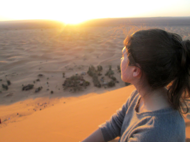 Watching the sunrise over the Sahara Desert.