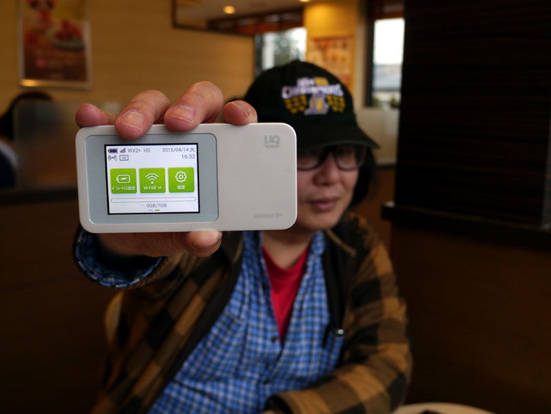 Speed Wi-Fi NEXT W01を手にポーズを ...