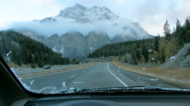 View of Cascade mountain in Banff National Park from the trans canada highway. Mountain is snow capped, mist hangs low around it.
