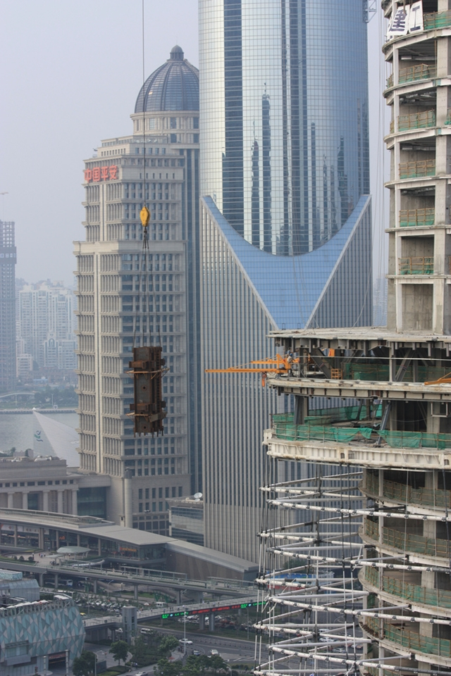 Big piece of steel being lifted by the crane with Shanghai buildings in the background