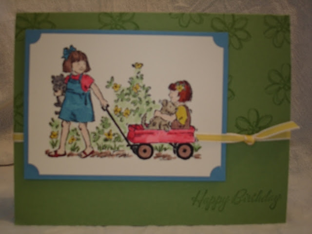 Little girl's birthday card with the image of one girl pulling a friend in a little red wagon.
