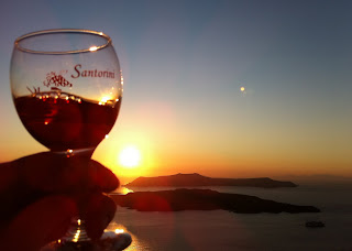 Holding a glass of Vinsanto with the sun setting over the Santorini volcano in the caldera.