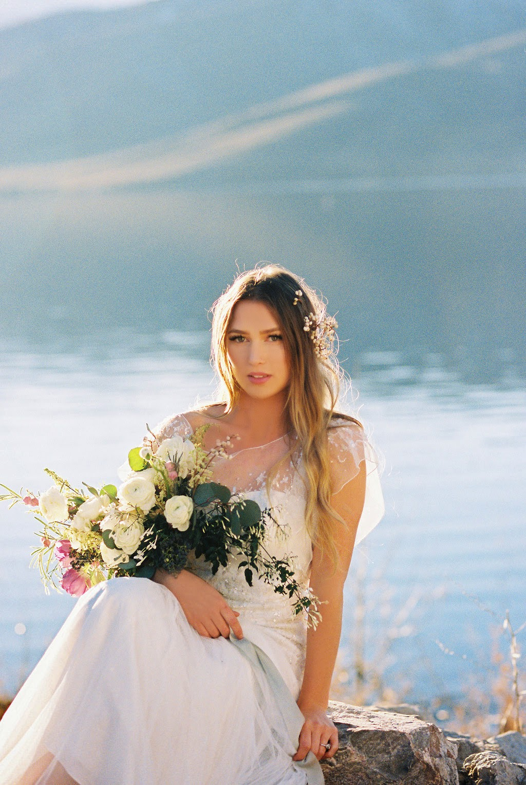 beautiful lakeside bride in a beaded flutter sleeve dress with tallow berry hairpiece and a late winter white and purple bouquet tied with hand dyed soft blue silk and willow ribbon