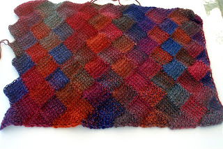 rainbow colored diamonds and triangles make up this crocheted entrelac shawl