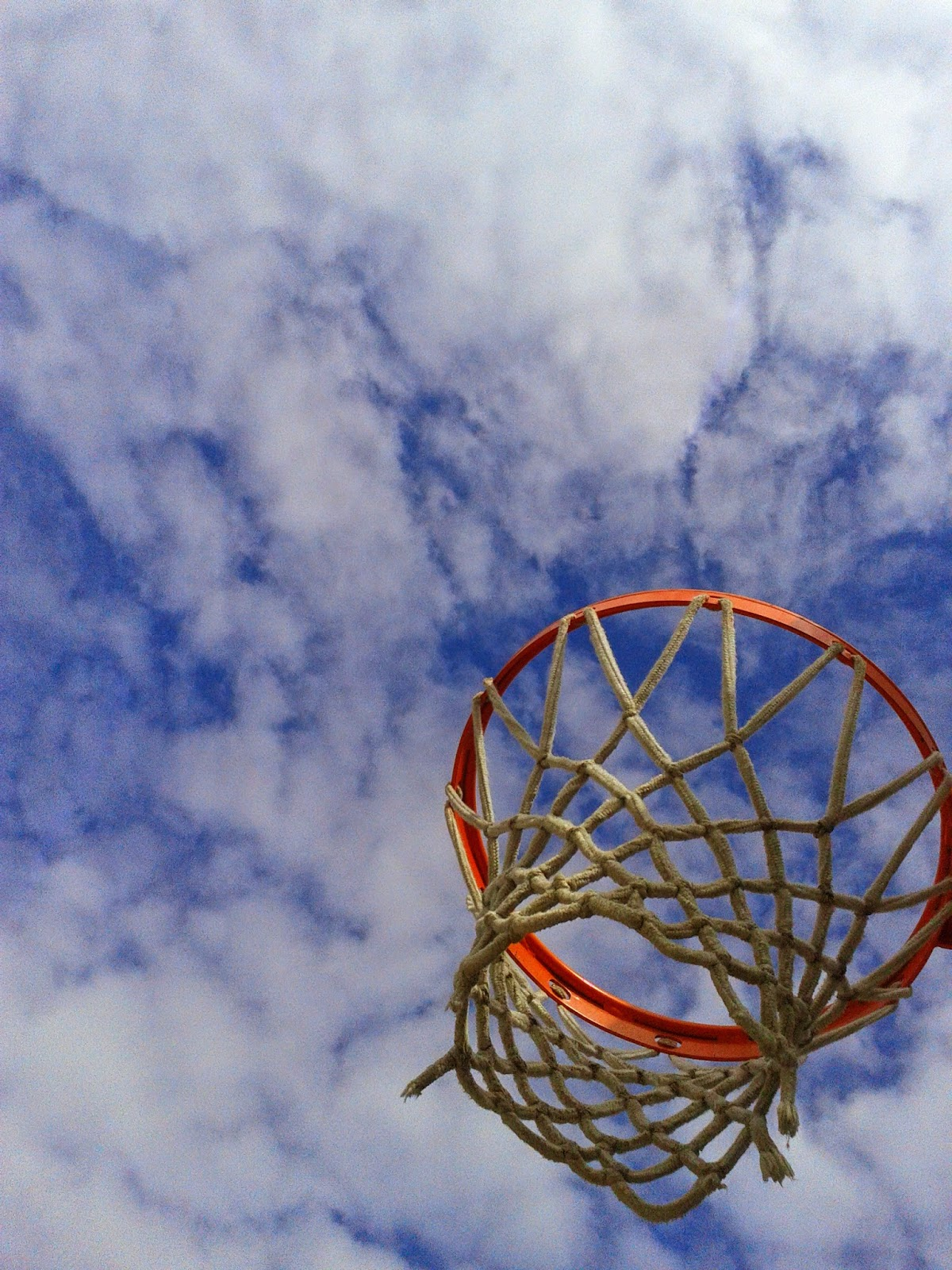 Basketball net rim amongst the blue sky and clouds