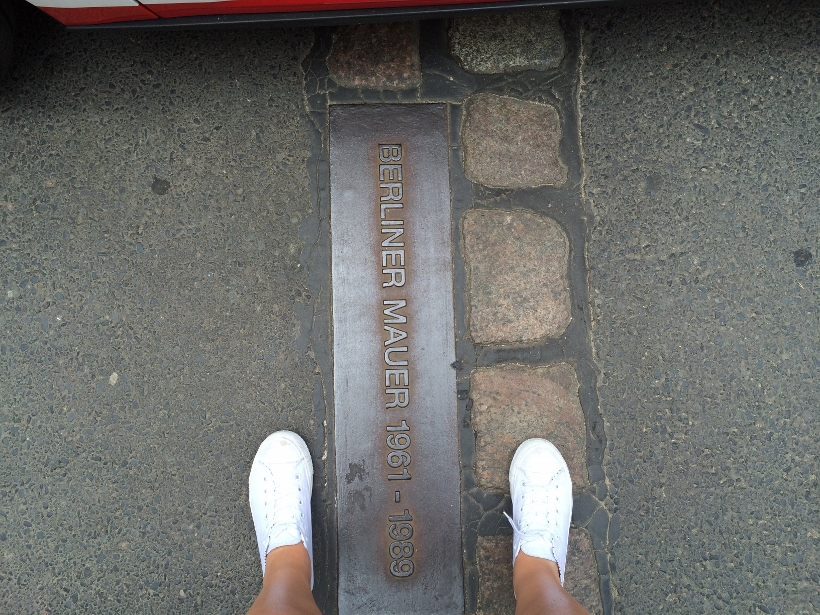 standing over berlin wall