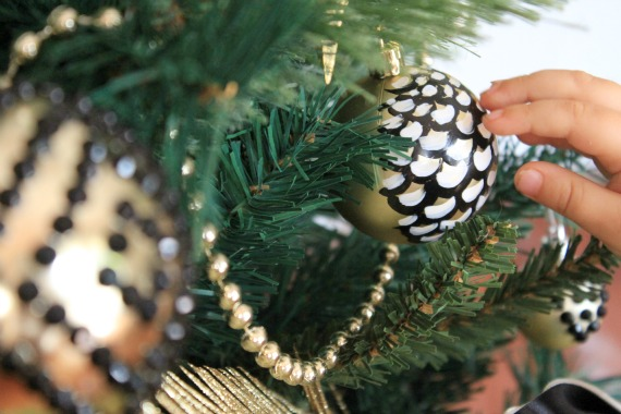 child's hand touching black and gold diy christmas ornament on decorated tree
