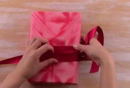 Gambar memasang pita pada bungkus kado