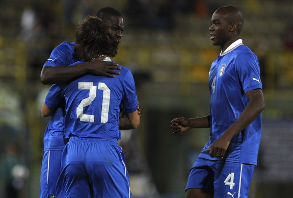 Andrea Pirlo embraces teammate Mario Balotelli after scoring Italy's third goal against San Marino