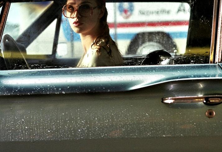 Une dame dans l'auto avec des lunettes et un fusil