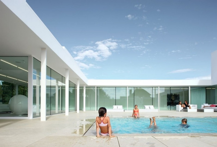 Kids in the swimming pool of Minimalist Home by Beel & Achtergael Architects