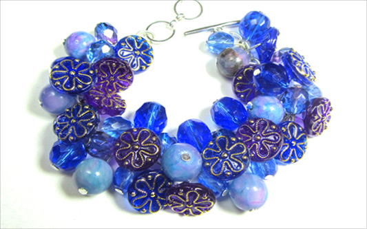 Dramatic bracelet has stunning blue and purple flower buttons and clusters of czech beads