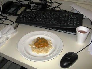Small plate of chicken korma surrounded by keyboard, mouse and telephone